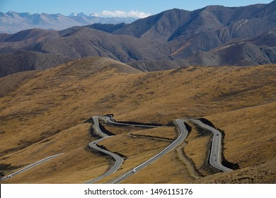 Spectacular view of a winding mountain road leading to Mount Everest base camp. Asphalt road leads tourists across the steep mountains in the Himalayas. Scenic view of a mountain road in sunny Tibet.