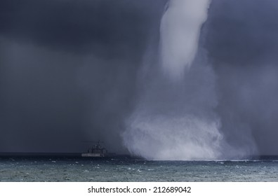 Spectacular waterspout approaching a boat