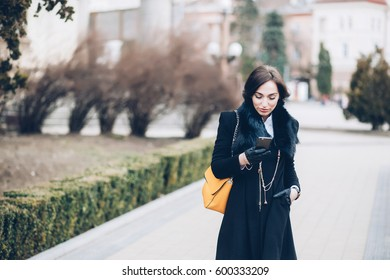 Spectacular young brunette, business woman outside fashionable and healthy with gadget