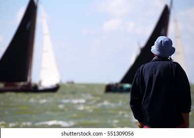 A spectator viewing the traditional Frisian wooden sailing ships, The Netherlands