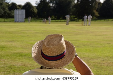 Spectator wearing sun hat at cricket match in English village.