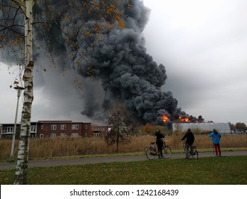 Spectators along the public road watch an extensive fire destroying the large building of a  construction market in a residential area. APELDOORN, THE NETHERLANDS - 27 NOVEMBER 2018