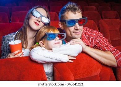 The spectators sitting in the cinema and watching movie  with cup of cola. Concept of a variety of human emotions.