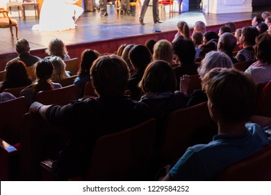 Spectators at a theater performance, in a cinema or at a concert. Shooting from behind. The audience in the hall. Silhouettes of people.