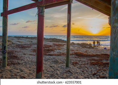 Spectators watching the sunrise from under a wooden deck with paint and graffiti on the poles