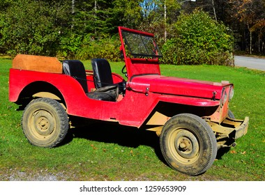 Speculator, NY - October 18, 2017:  A dirty old red 1946 Jeep CJ-2A parked on a lawn.