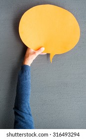Speech bubble. Close-up of man stretching out empty speech bubble against grey background