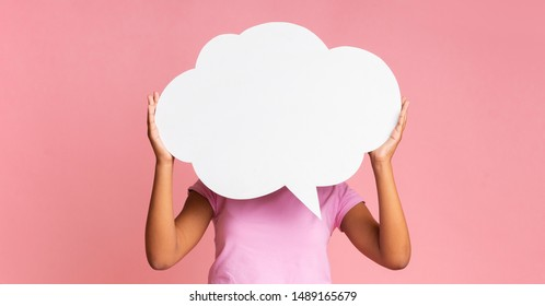 Speech bubble at pink. Unrecognizable black woman holding it in front of her head at studio background, empty space