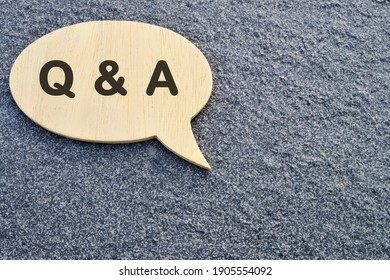 Speech bubble with Q and A on concrete background.
