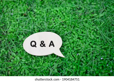 Speech bubble with Q and A on grass background.