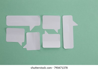 Speech bubbles sticky notes composition, teal background. Conversation chat concept with blank paper notes