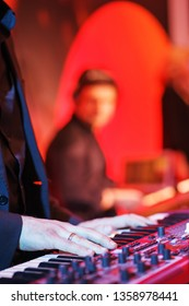 Speech by musicians on stage. Close-up on a musician. Hands and musical instrument closeup. Show in a nightclub, entertainment for adults. Guitar, keys and drum - musical instruments.
