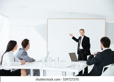 Speech of elderly business man on conference which standing near the board with his colleagues by the table
