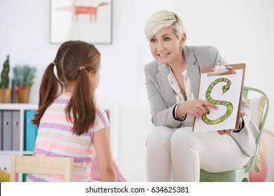 Speech pathologist with young girl learning the alphabet