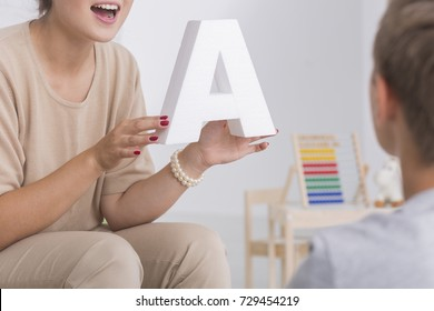 Speech therapist in beige costume holds letter A and speaks to kid during class session