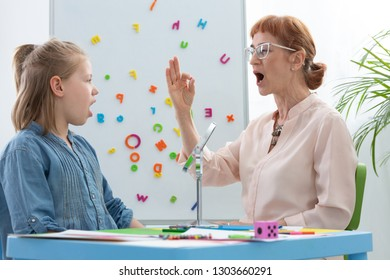 Speech therapist and girl learning vowels