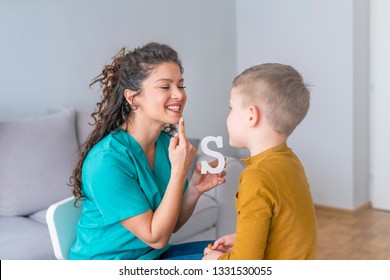 Speech therapist and little patient training articulation. Speech therapist teaches the boys to say the letter S. Shot of a speech therapist during a session with a little boy