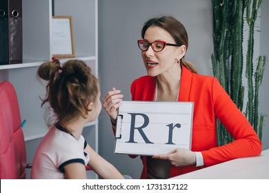 Speech therapist teaches the girls to say the letter R. Female Speech Language Therapist Teaching Preschool Kid Sound Pronunciation, Stuttering Cute Child Having Stutter.