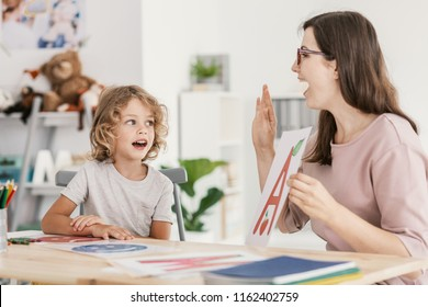 Speech therapist teaching letter pronunciation to a young boy in a classroom