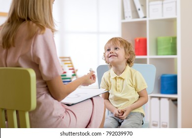 Speech therapist working with child boy in office or home