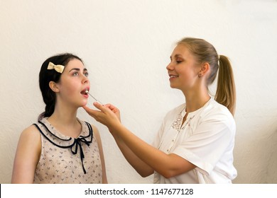 the speech therapist works with the patient over the speech, showing the logopedic probe the position of the tongue.