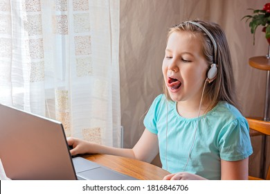 Speech training concept. Little girl uses a laptop to study at home with a teacher, a speech therapist. Distance learning. A kid doing exercises for correct pronunciation. - Shutterstock ID 1816846706