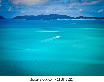 Speed Boat leaves wake in turquoise waters of Hill Inlet in Whitsundays, Queensland, Australia. Swirling ribbons of blue and azure from white sands of whitehaven beach.