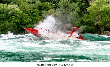 Speed boat on rough river with rocks and trees in the background.