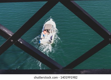 Speed boat seen through abstract framed iron grate in daylight