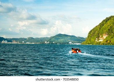 Speed boat travelling on the sea. The tropical islands and a beautiful cloudy sky are visible in the background. Shot in Langkawi