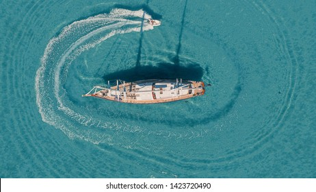 Speed boating around anchored sail yacht