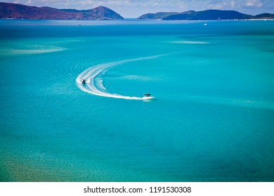 Speed Boats chase each other leaving wake in turquoise waters of Hill Inlet in Whitsundays, Queensland, Australia. Swirling ribbons of blue and azure from white sands of whitehaven beach.