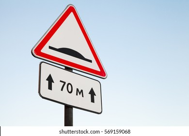 Speed Bump. Warning road sign over bright blue sky background