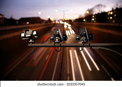 Speed camera monitoring busy traffic road at night. Highway underpass traffics present, long exposure applied lights trail present.