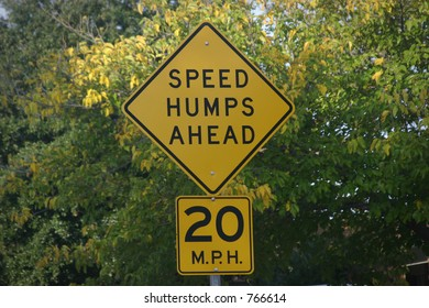 Speed humps sign with trees