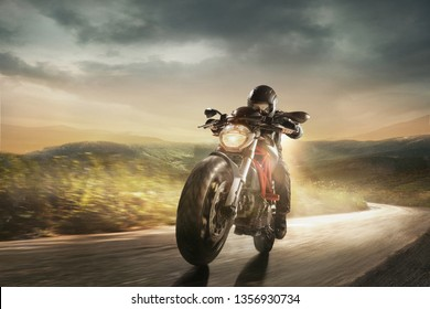 Speed of inspiration, aspiration and wild energy on the road. Get faster. Biker in black helmet is driving the handsome sport motorbike near meadows and mountains in cloudly evening on country side.