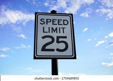 Speed Limit 25 mph Street Sign Close up with Cumulus Clouds in background.