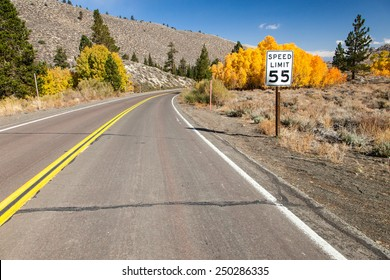 Speed limit by the road with fall colors in the background - no cars.