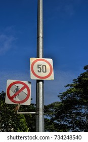 Speed limit and Pedestrian crossing prohibition sign. Do not exceed the speed limit indicated in 50km/h. Pedestrians must not cross the road in the zones indicated.