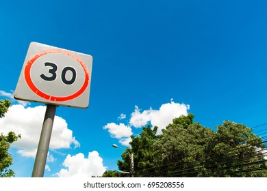 Speed limit sign with clear sky and trees