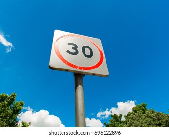 Speed limit sign with clear sky and trees around