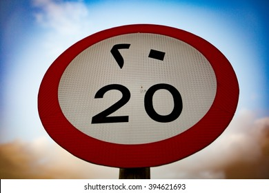Speed limit sign with Eastern Arabic and Western Arabic numerals with cloudy sky background.
