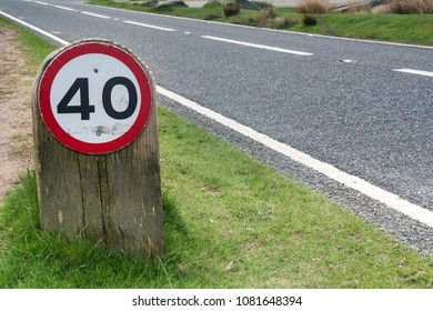 Speed limit sign on grass verge by side of road