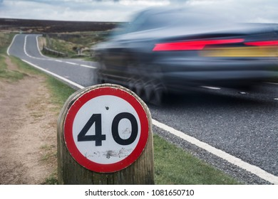 Speed limit sign on rural road with car