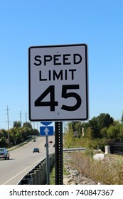 The speed limit sign on the side of the highway.