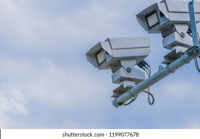 Speed radar cameras mounted on metal pole against blue sky with puffy white clouds.