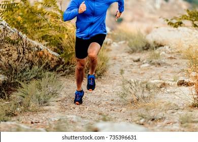 speed running on mountain trail male athlete runner