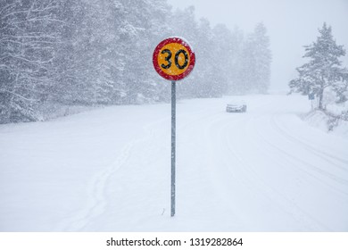 A speed sign by a snowy country road in Sweden.