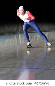 Speed skater accellerating towards the finish line of a long distance race on an ice rink
