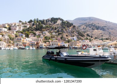 speedboat lying in the port of Symi with the skyline of the village in the background